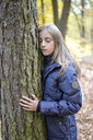 Portrait of girl with eyes closed touching tree in the woods - BFRF01941