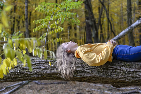 Girl lying on tree trunk in autumnal forest relaxing - BFRF01944