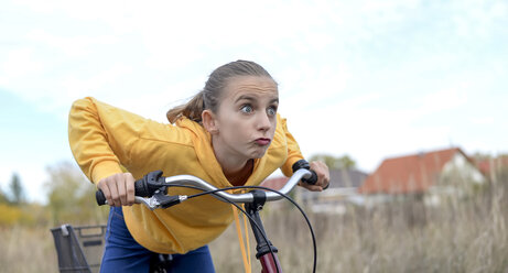 Portrat of girl with bicycle wearing yellow hooded jacket - BFRF01947