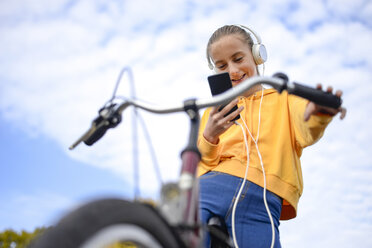 Smiling girl with headphones and bicycle looking at smartphone - BFRF01950
