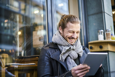Portrait of laughing young man in front of a cafe looking at tablet - FMKF05345