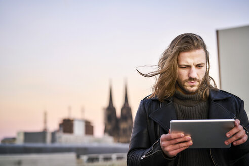Germany, Cologne, portrait of bearded young man using digital tablet - FMKF05348