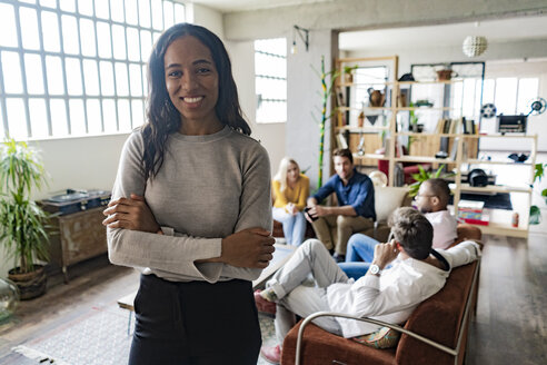 Portrait of smiling young businesswoman with coworkers in background in loft office - GIOF05159