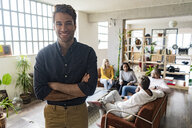Portrait of smiling young businessman with coworkers in background in loft office - GIOF05162