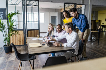 Business team having a meeting in loft office looking at laptop together - GIOF05186