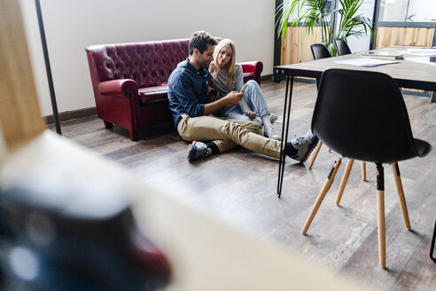 Young man and young woman sitting on the floor in loft office sharing cell phone - GIOF05201