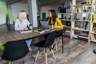 Two happy young businesswomen sitting at conference table in loft office - GIOF05207