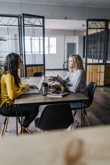 Two young businesswomen talking at conference table in loft office - GIOF05210