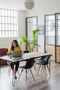 Young businesswoman sitting at desk in loft office using cell phone - GIOF05222