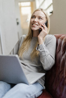 Smiling young woman sitting on couch with laptop talking on cell phone - GIOF05228