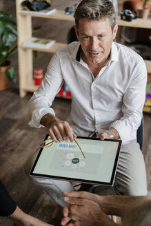 Businessman explaining a mind map on tablet screen during a presentation in loft office - GIOF05231