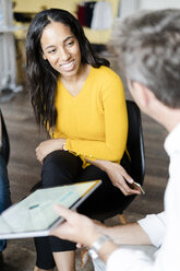 Portrait of smiling businesswoman listening to a presentation in loft office - GIOF05234