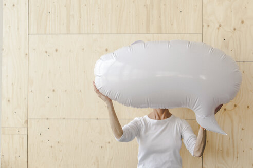 Woman standing in office, holding inflatable speech bubble in front of her face - RIBF00772