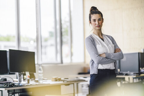 Portrait of a beautiful young woman, standing in office, with arms crossed - RIBF00778