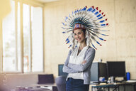 Young woman wearing Indian headdress, standing in office, with arms crossed - RIBF00787