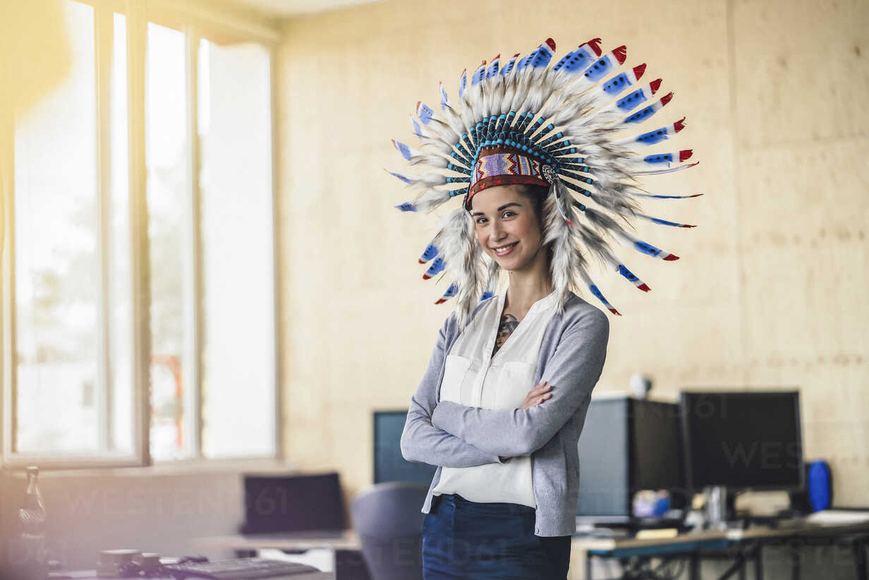 Young woman wearing Indian headdress, standing in office, with arms crossed - RIBF00787 - Richárd Bellevue/Westend61