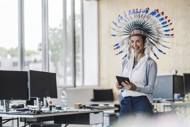 Young woman wearing Indian headdress, standing in office, using digital tablet - RIBF00790