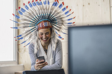 Young woman wearing Indian headdress, standing in office, usinag smartphone - RIBF00793