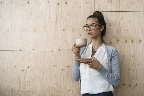 Young woman working in creative office, taking a break, drinking coffee from wooden cup - RIBF00796