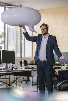 Businessman standing in office, holding inflatable speech bubble - RIBF00799