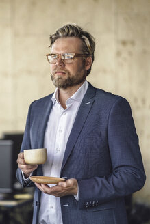 Businessman standing in office, drinking coffee from a wooden cup - RIBF00802