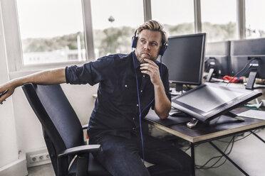 Tired graphic designer using digital tablet, wearing headphones - RIBF00814