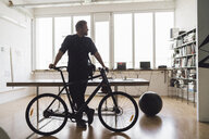 Man standing in office with his bicycle - RIBF00820