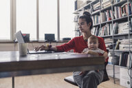 Working mother with baby on her lap, sitting in office, using laptop - RIBF00823