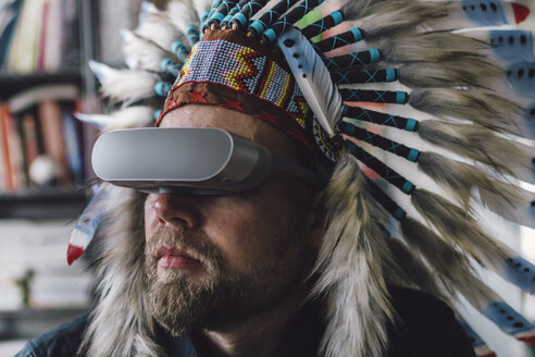 Man wearing Indian headdress and VR glasses in office - RIBF00829