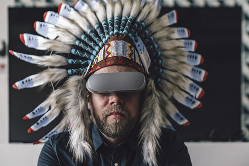Man wearing Indian headdress and VR glasses in office - RIBF00832