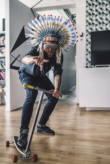 Man wearing Indian headdress and VR glasses in office, using kick scooter - RIBF00835