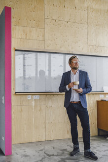 Businessman standing in his office in front of whiteboard, drinking coffee from a wooden cup - RIBF00847