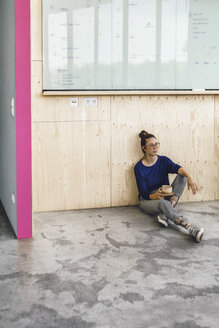Young woman taking a break in office, drinking coffee from a wooden cup - RIBF00850