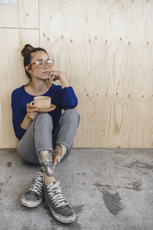Young woman taking a break in office, drinking coffee from a wooden cup - RIBF00853