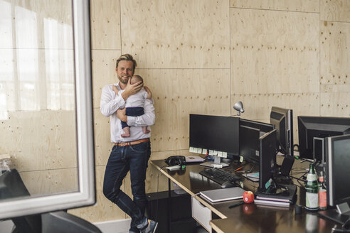 Working father standing in office, holding his son - RIBF00856