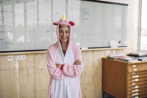 Woman wearing unicorn onesie, standing in front of whiteboard, laughing - RIBF00859