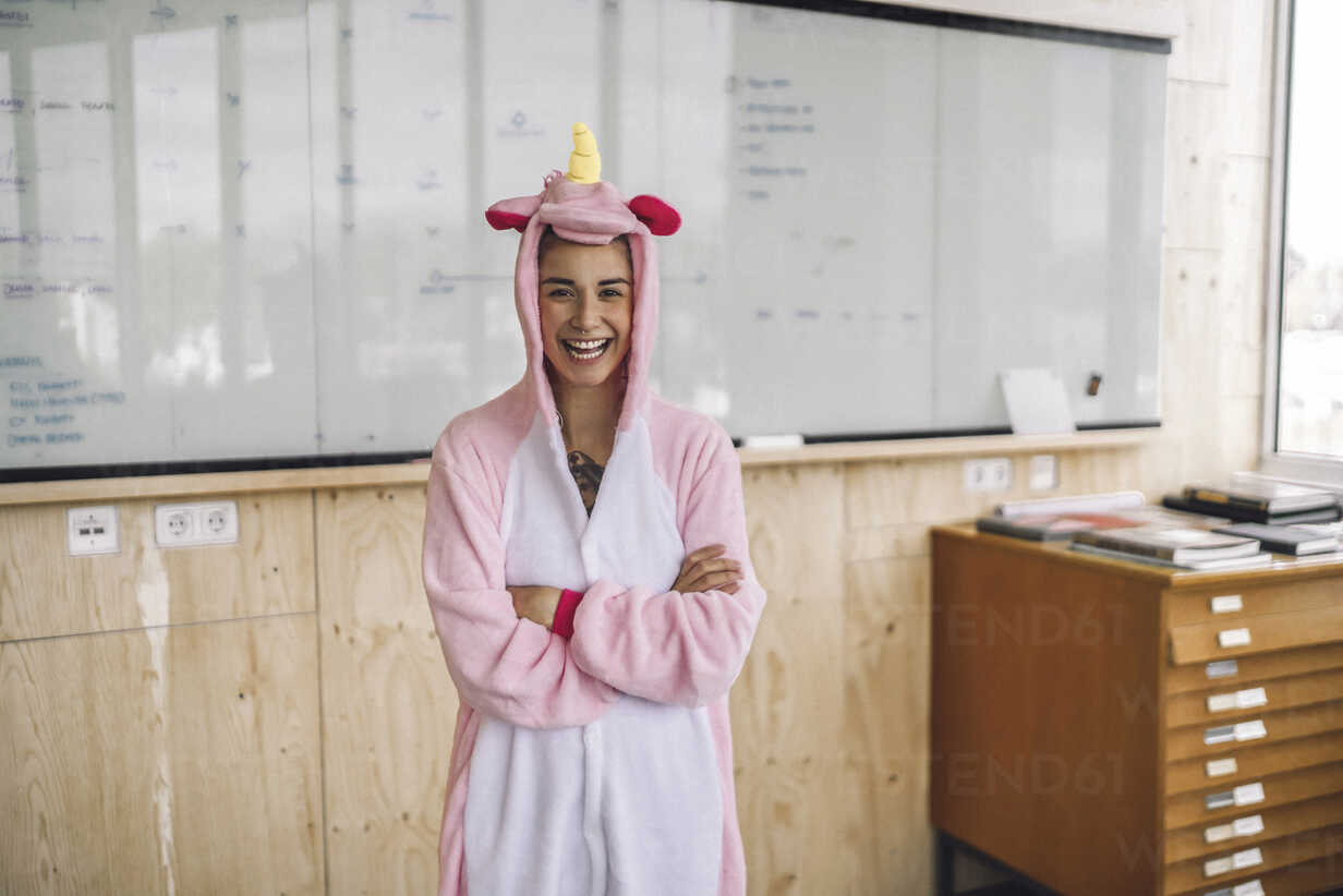 Woman wearing unicorn onesie, standing in front of whiteboard, laughing - RIBF00859 - Richárd Bellevue/Westend61