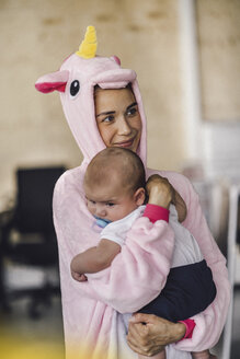 Young mother wearing unicorn onesie, standing in office, holding her son in her arms - RIBF00862