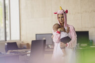 Young mother wearing unicorn onesie, standing in office, holding her son in her arms - RIBF00865