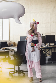 Young mother in unicorn onesie, holding her son in her arms, with speech bubble over her head - RIBF00868