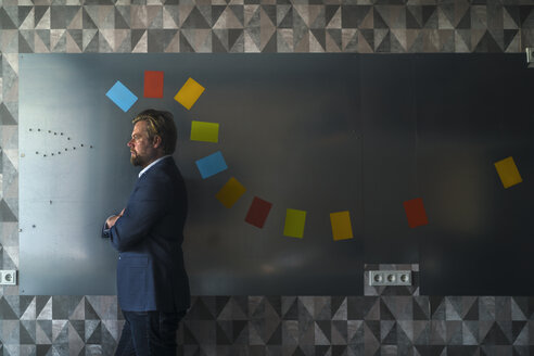 Businessman standing in front of magnet wall with a colorful headdress, made from sticky notes - RIBF00874