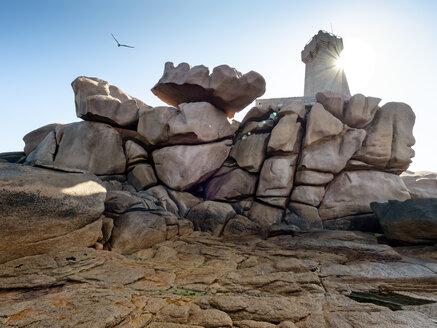 France, Bretagne, Plougrescant, Cote de Granit Rose, rock formation at Phare de Mean Ruz against the sun - LAF02201