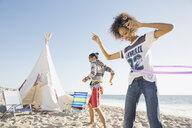 Couple hula hooping on beach - HEROF00328