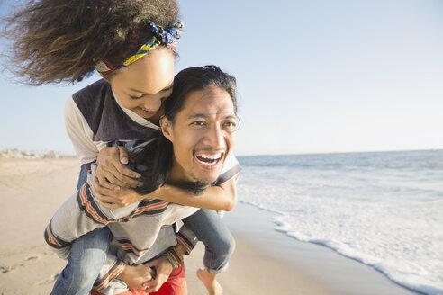 Man piggybacking woman on beach - HEROF00349