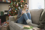 Woman hand writing Christmas cards in living room - HEROF00400