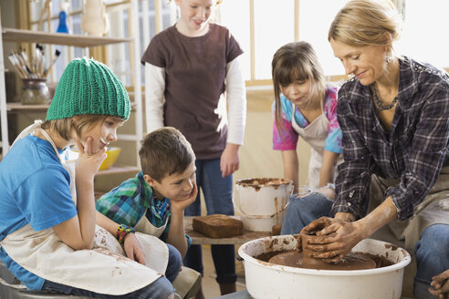 Students watching instructor on potters wheel - HEROF00403