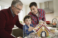 Three generation family decorating gingerbread house together - HEROF00469