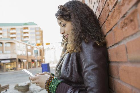 Woman text messaging against brick wall - HEROF00472