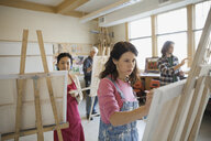 Woman painting on easel in art studio - HEROF00511