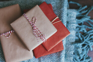Stack of wrapped Christmas presents on a blanket - FSIF03405